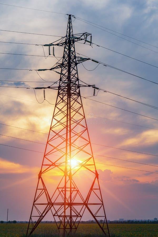 Pylônes et lignes électriques de l'électricité, au coucher du soleil photo stock