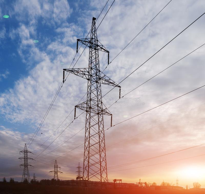 Pylônes et lignes électriques de l'électricité, au coucher du soleil photos libres de droits