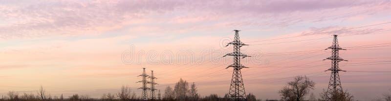 Pylônes et lignes de l'électricité au crépuscule. Panorama. image libre de droits