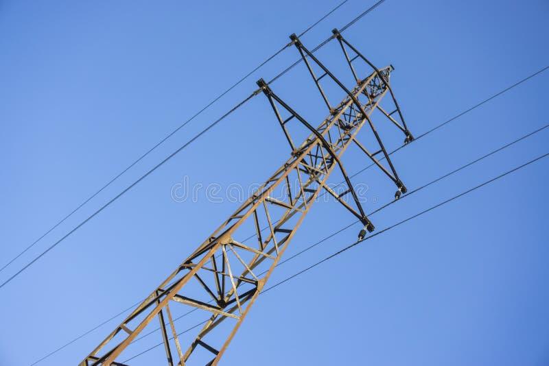 Pylône à haute tension de grille d'alimentation contre le ciel bleu images stock