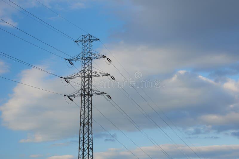 Pylône de transmission de l'électricité silhouetté contre le ciel bleu photographie stock libre de droits