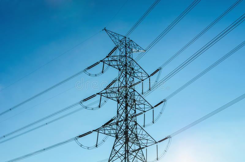 Pylône de transmission de l'électricité silhouetté contre le ciel bleu images stock
