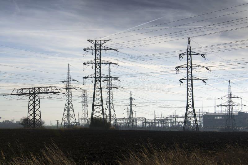 Pylônes de l'électricité avec le fond bleu de ciel nuageux de centrale de distribution images libres de droits