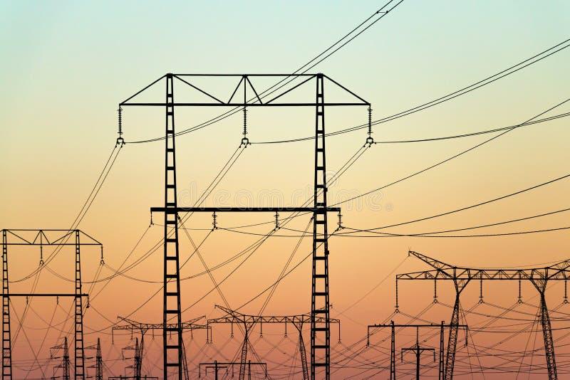 Pylônes de l'électricité sur le ciel coloré de soirée photos stock