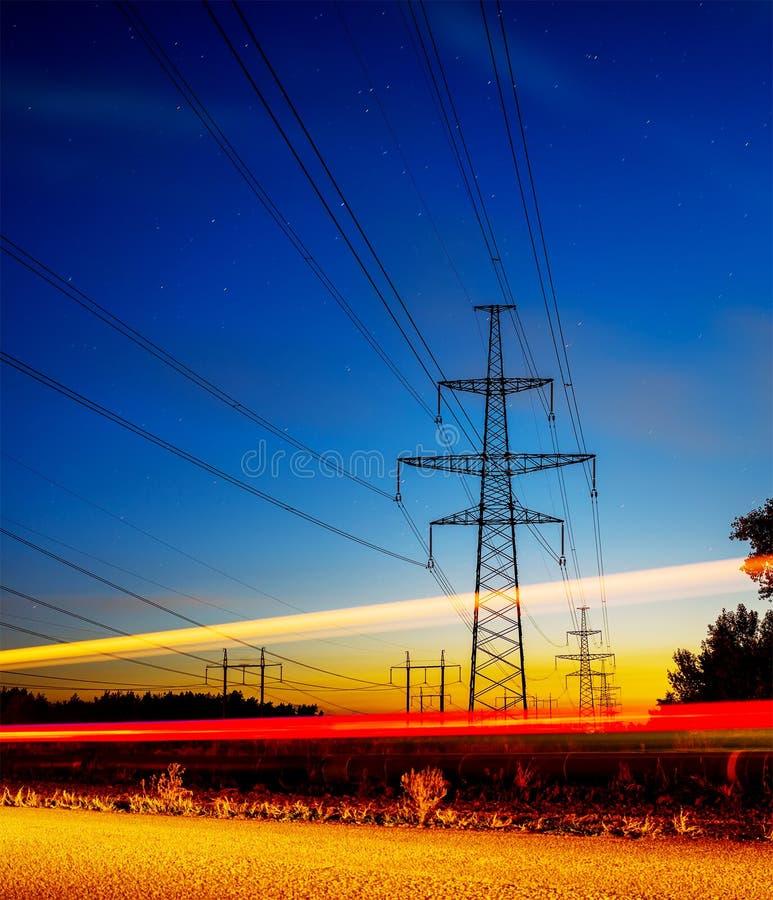 Pylônes et lignes à haute tension de l'électricité la nuit avec des feux de signalisation dans l'avant photos stock