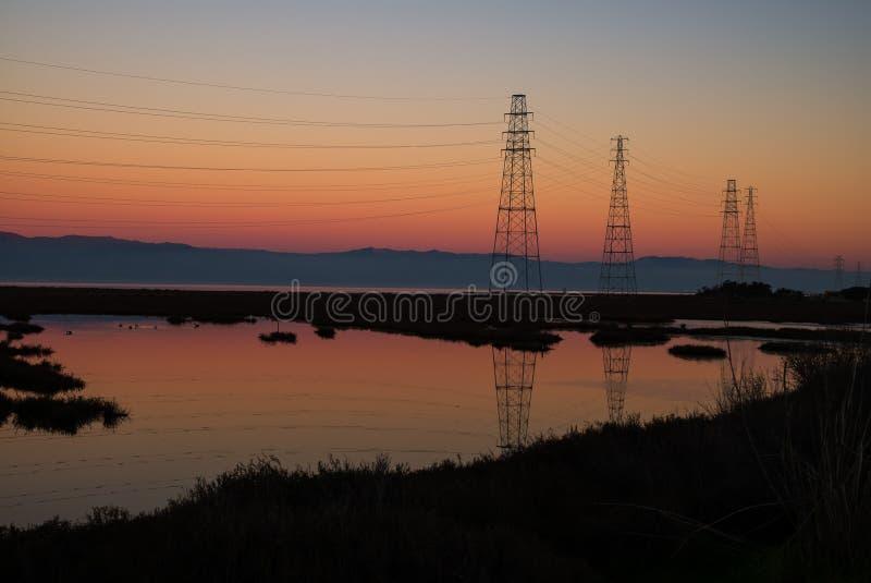 Pylônes et montagne de coucher du soleil image stock