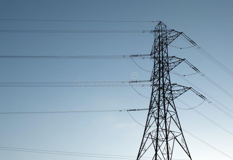 Pylon di alta tensione con cavi multipli ad alta tensione messi a tacere contro un cielo azzurro fotografia stock libera da diritti