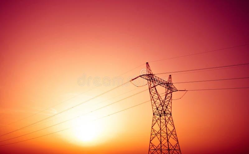 Pylon och kraftledningar i solnedgång fotografering för bildbyråer