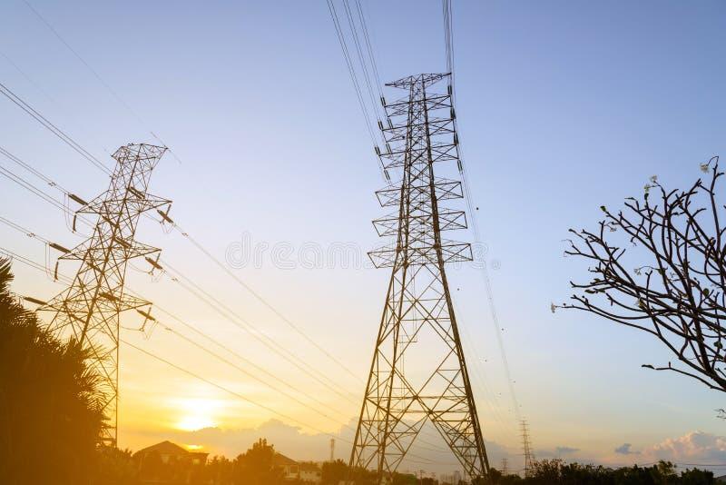 Pylon systeem van de hoogspanningselektriciteit bij zonsondergang stock foto