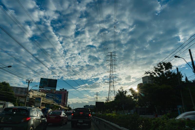 Pylonen en de lijnen van de elektriciteitsmacht bij zonsondergang en duidelijke clounds stock afbeeldingen