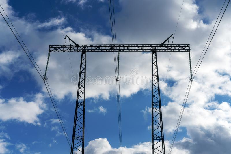 Pylons of high-voltage power lines and a blue sky with clouds stock photo