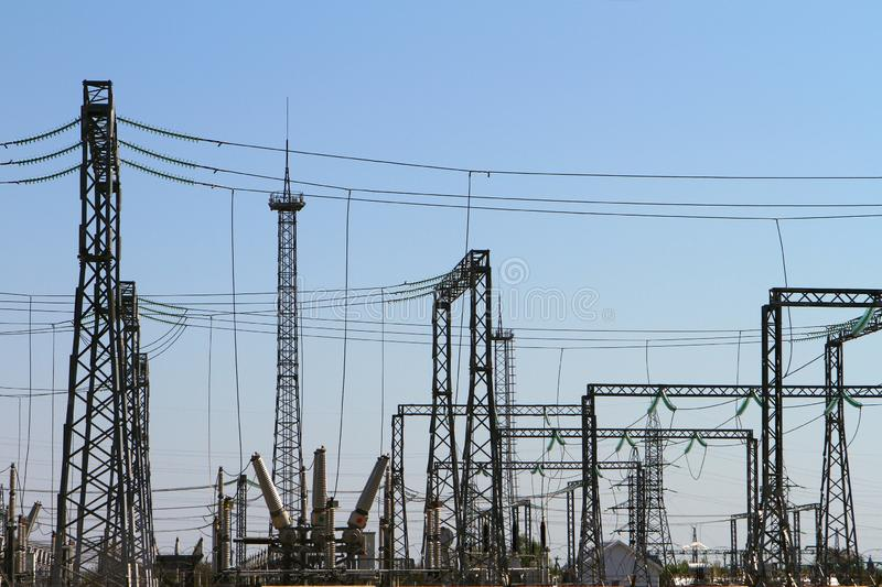 Pylons of high-voltage power lines and a blue sky. Electric power substation stock photo