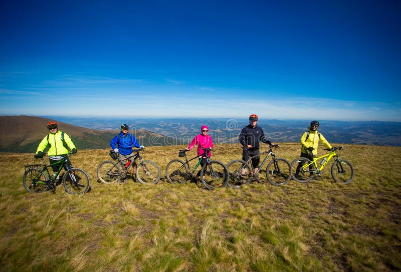 Pylypets, Ukraine - 15 September, 2019: Five friends on bicycles are happy on top of mountains stock images