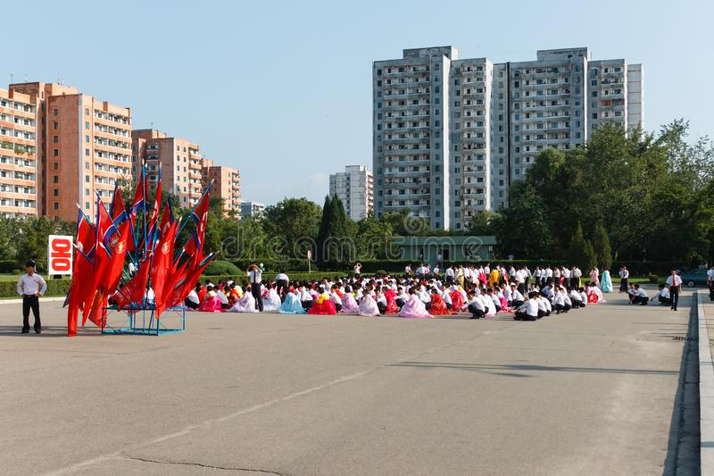 Pyongyang, North Korea. July 27, 2014: Korean Men and women are sitting on the square in anticipation of the start of mass dances dedicated to the day of royalty free stock image