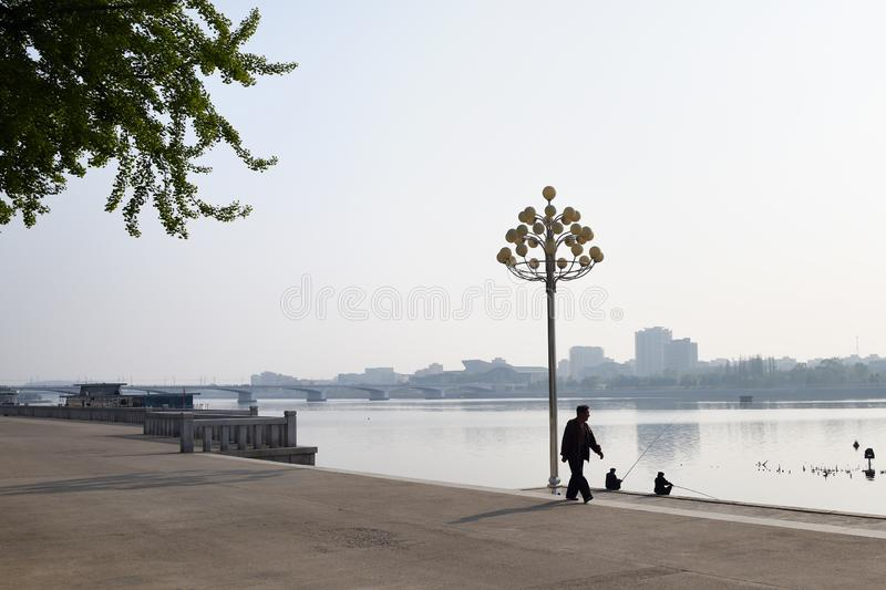 Pyongyang, North Korea. Kim Il Sung square embankment. Pyongyang, North Korea - May 1, 2019: Locals fishermen catch a fish on waterfront on Kim Il Sung square at stock photography