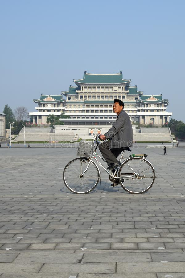 Pyongyang, North-Korea. Kim Il Sung square. Pyongyang, North-Korea - May 1, 2019: A man on a bicycle crosses the central square of Kim Il Sung. Great People`s stock photos