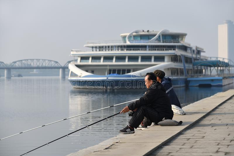 Pyongyang, North Korea. Kim Il Sung square. Pyongyang, North Korea - May 1, 2019: Street scene. Two fishermen catch a fish on waterfront on  Kim Il Sung square stock image