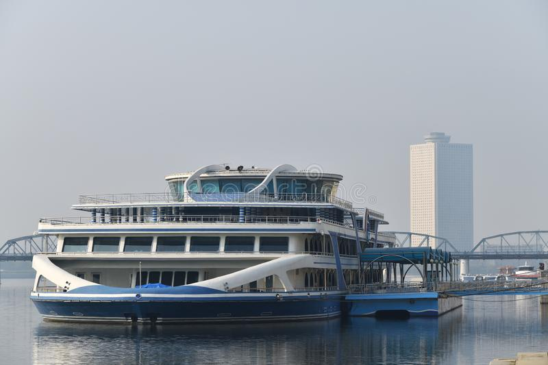 Pyongyang, North Korea. Pyongyang, North Korea - May 1, 2019 Waterfront on Kim Il Sung square at the morning. Deborkade, floating restaurant on the Taedong royalty free stock photos