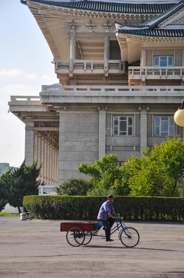 Pyongyang, North-Korea, 09/07/2018: a lonely haul bike is passing by the cultural palace of the people. Pyongyang, North-Korea, 09/07/2018: a lonely haul bike royalty free stock photography