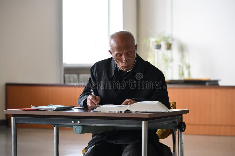 Pyongyang, North Korea. Man in library. Pyongyang, North Korea - April  29, 2019: Senior man in Great People`s Study House studies the Juche philosophy book stock photography