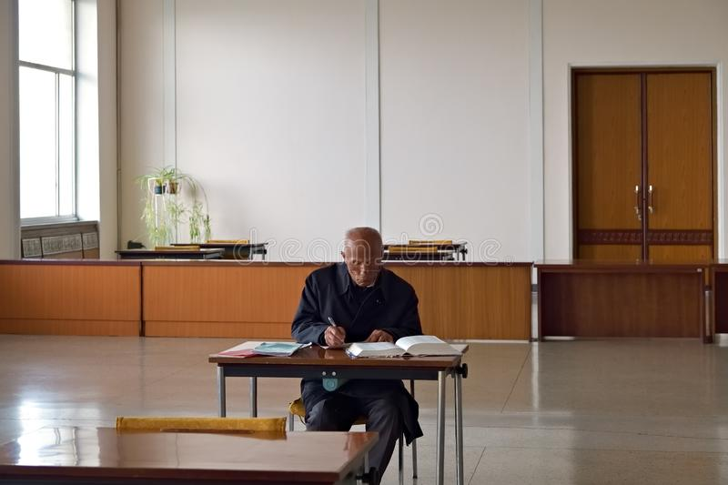 Pyongyang, North Korea. Man in library. Pyongyang, North Korea - April  29, 2019: Senior man in Great People`s Study House studies the Juche philosophy book royalty free stock photos