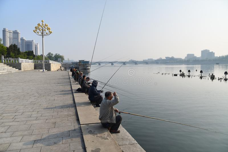 Pyongyang, North Korea. Kim Il Sung square. Pyongyang, North Korea - May 1, 2019: Locals fishermen catch a fish on waterfront on Kim Il Sung square at the royalty free stock images