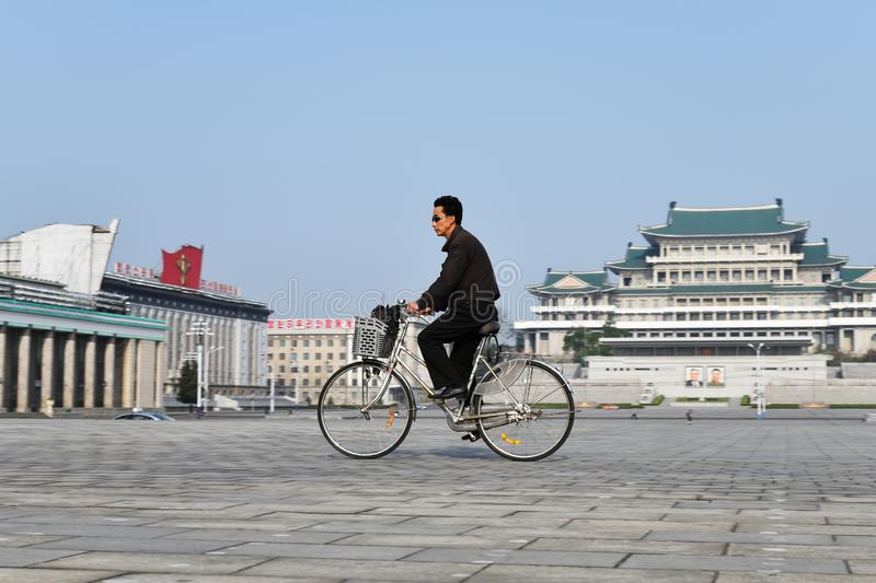 Pyongyang, North Korea. Kim Il Sung square. Pyongyang, North Korea - May 1, 2019: A man on a bicycle crosses the central square of Kim Il Sung. Great People`s stock photography