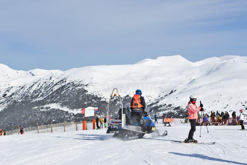 PYRÉNÉES, ANDORRE - 8 FÉVRIER 2018 : délivrance sur un motoneige parmi des touristes sur des skis photos libres de droits