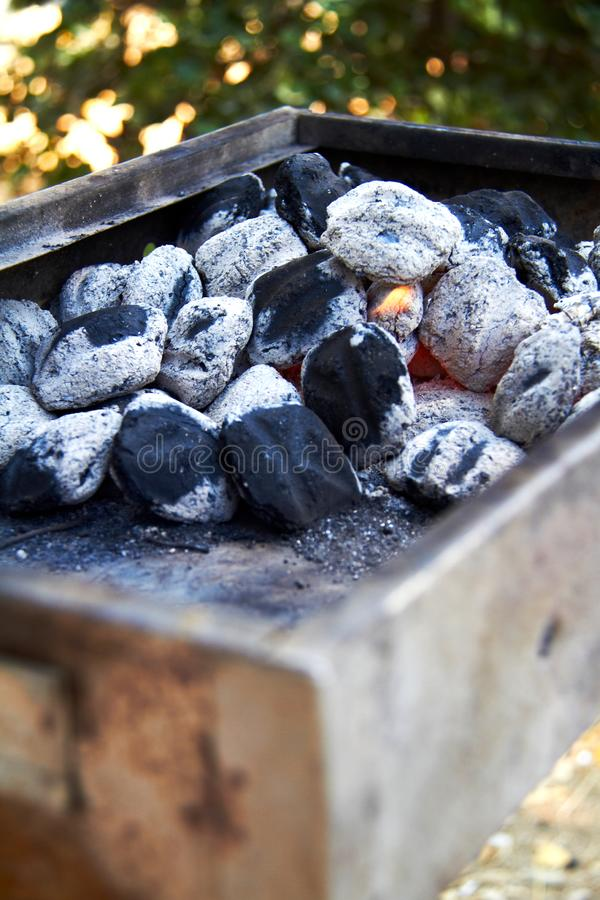 Pyra kol ligger på gallret, ordnar till för att grilla royaltyfri foto