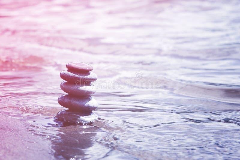 Pyramid av att balansera kiselstenar i vatten Zensymbol, mjuk rosa lila arkivbilder