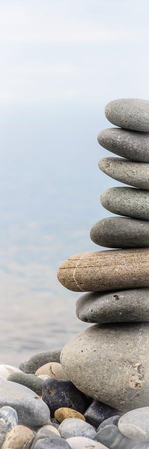 Pyramid av havsstenar p? kiselstenar av havskusten seascape Begreppet av j?mvikt och andlighet royaltyfri fotografi