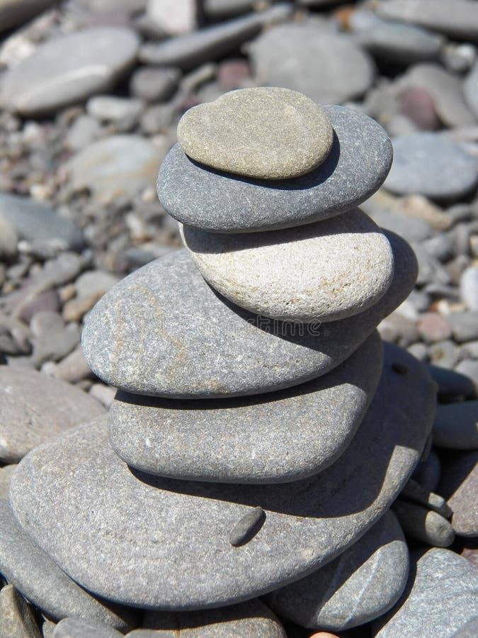 Pyramid av kiselstenar på en stenig strand royaltyfri bild