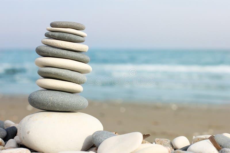 Pyramid av kiselstenar på stranden, närbilden och det fria utrymmet för text, Cypern arkivfoto