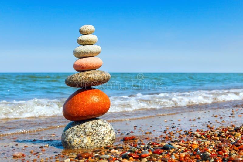 Pyramid av kulöra kiselstenar på en bakgrund av sommarhavet Begrepp av harmoni, jämvikt och meditationen fotografering för bildbyråer