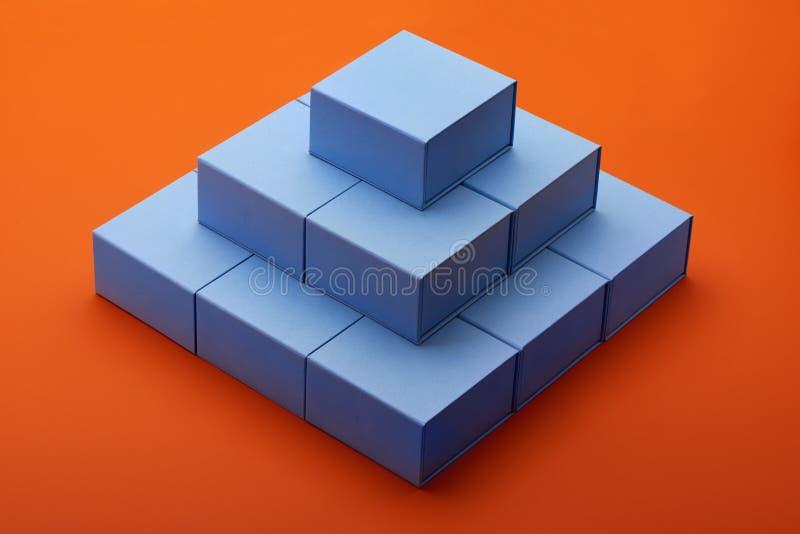 Pyramid av ljust - blåa gåvaaskar på orange pappers- bakgrund arkivbilder