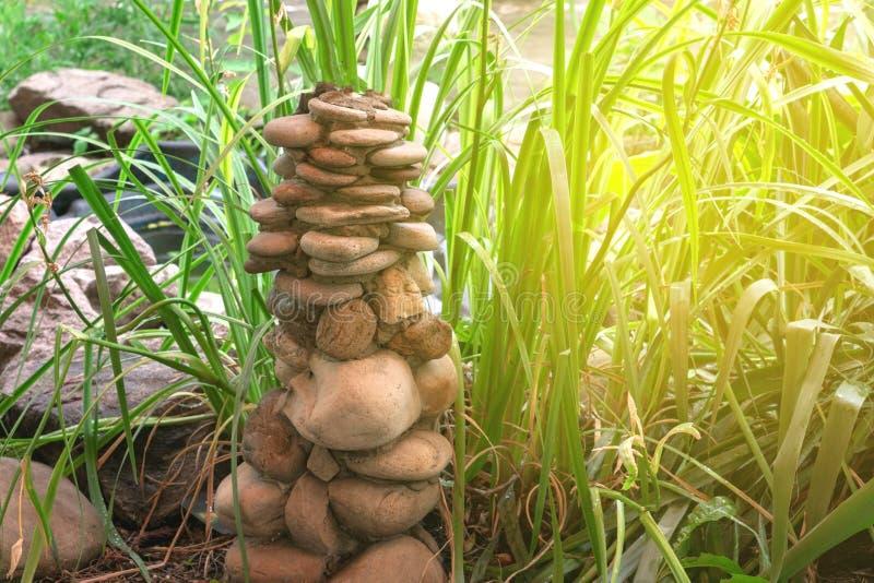 Pyramid av naturliga stenar på bakgrunden av grönt gräs royaltyfria foton