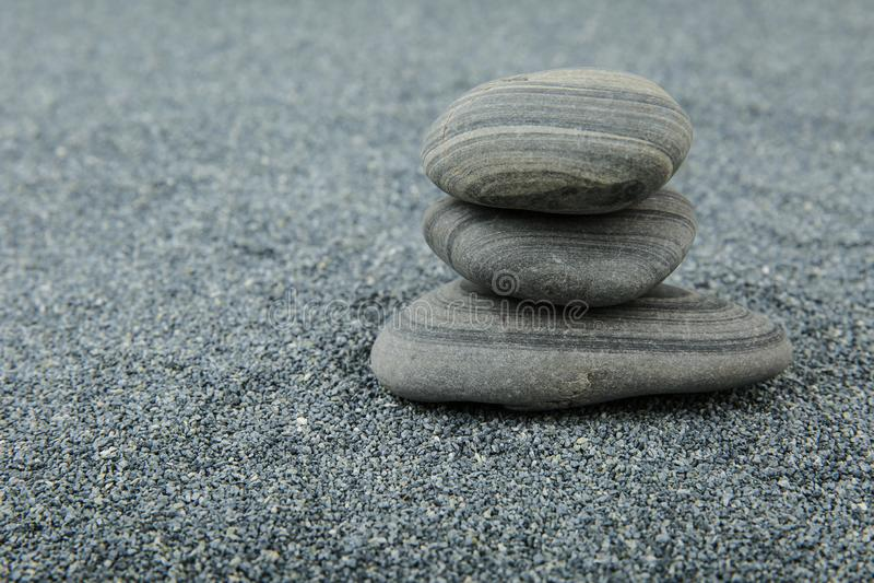 pyramid av stenar på grå sandbakgrund med fritt utrymme royaltyfria foton