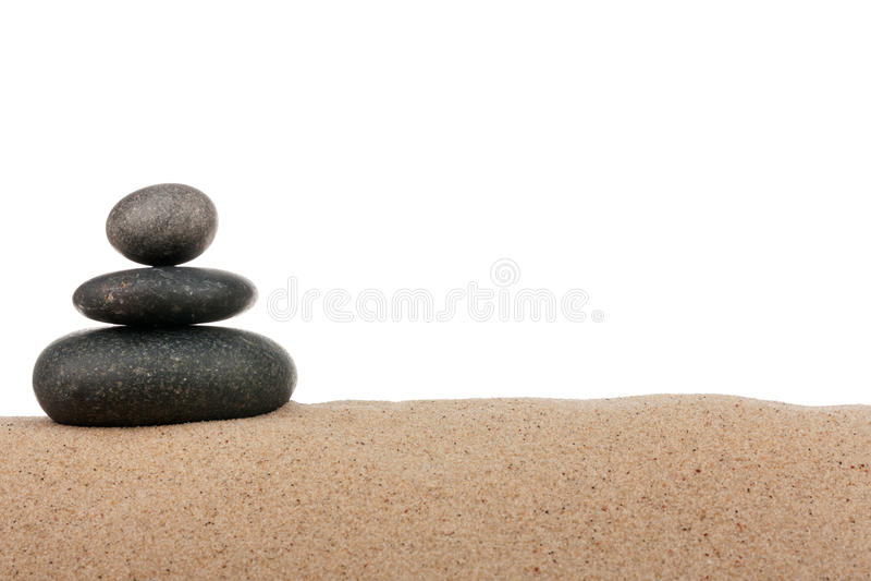 Pyramid av svarta stenar på sandstranden bakgrund isolerad white royaltyfria bilder