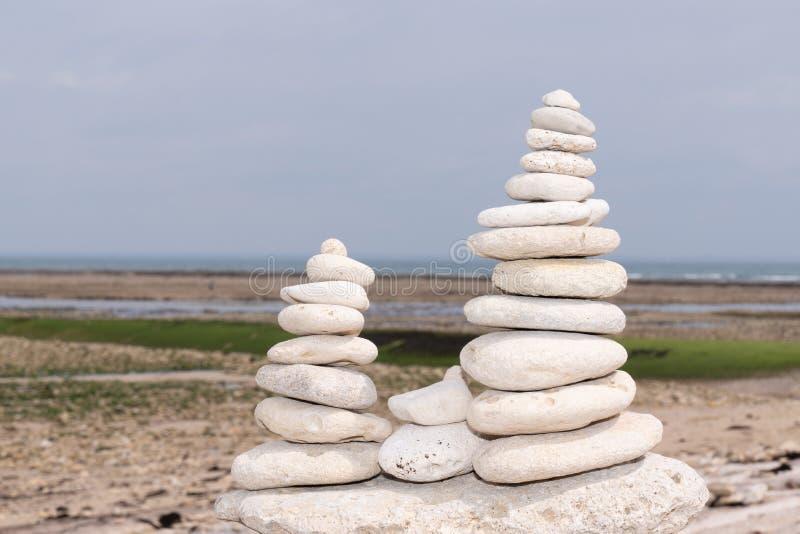 Pyramid av vita gråa stenar på den sandiga stranden på havbakgrund royaltyfria bilder