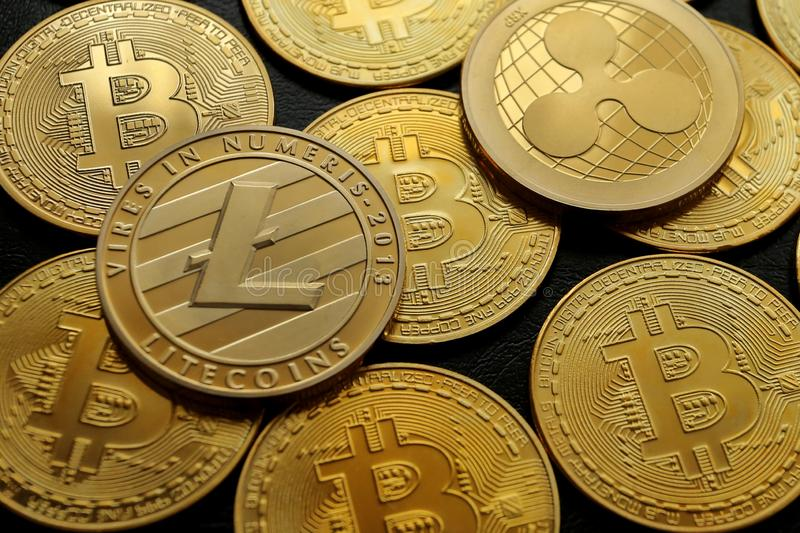 A pyramid of crypto currencies Bitcoin Ripple Litecoin. Cryptocurrency, a pyramid of gold and silver Bitcoins, Ripples and Litecoins on a black leather texture stock photography