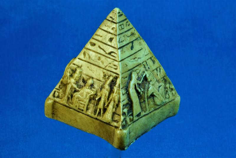 Pyramid of Egypt figurine souvenir on a blue background. stock photos