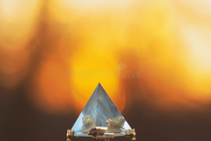 Pyramid för Crystal exponeringsglas på en bakgrund av en suddig sol och himmel för solnedgång för avkopplingmeditation och spådom royaltyfri foto