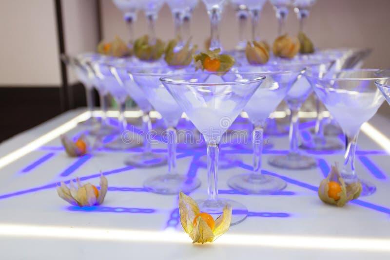 Pyramid från champagneexponeringsglas med physalisen på bröllopet royaltyfri foto