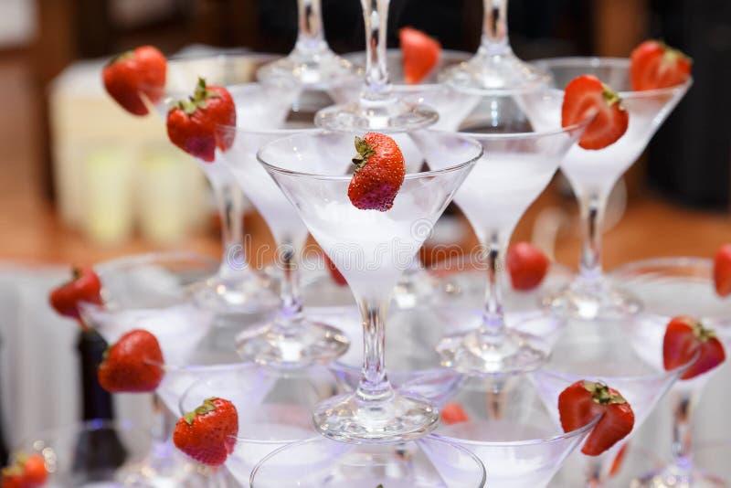 Pyramid från exponeringsglas av champagne med jordgubben på brölloppartiet arkivbilder