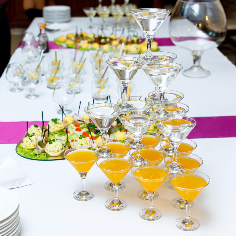 Pyramid of glasses with drinks and wine on banquet table stock image