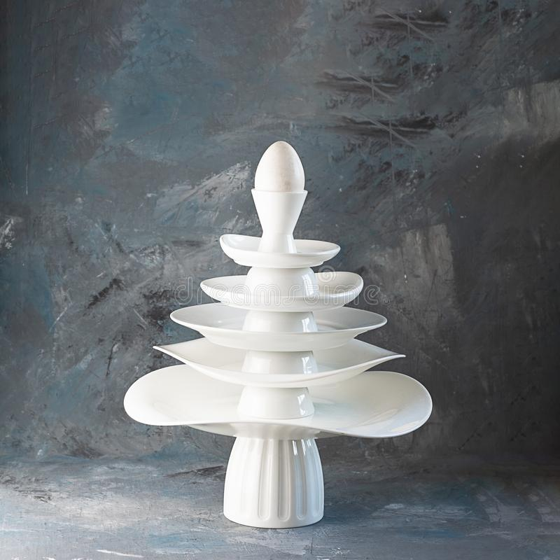 Pyramid made from white dishes, Christmas tree shape with egg on top on dark background. Creative concept about dishware, kitchen royalty free stock image