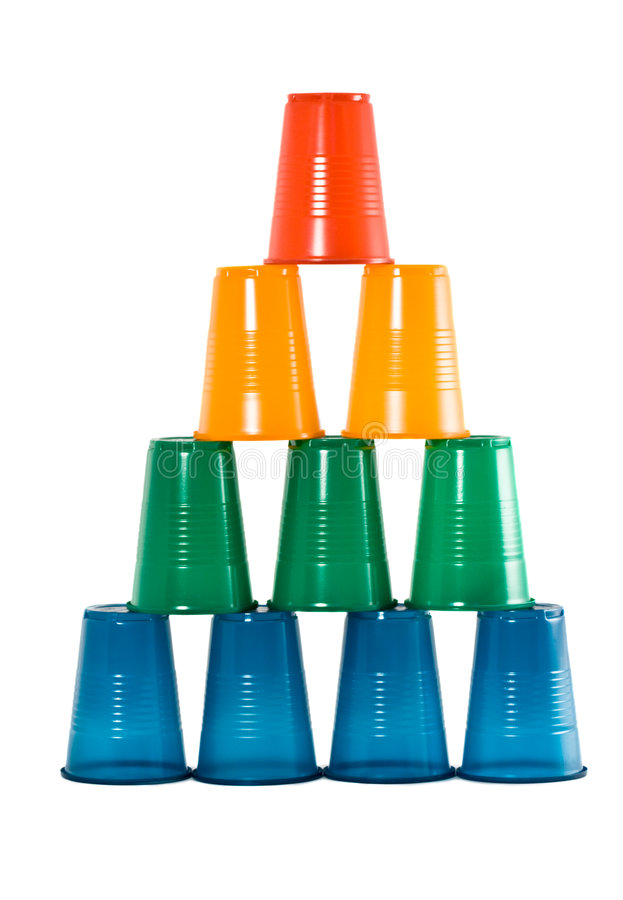 Pyramid from multi-coloured plastic glasses. Pyramid from multi-coloured disposable plastic glasses isolated on white background royalty free stock photos