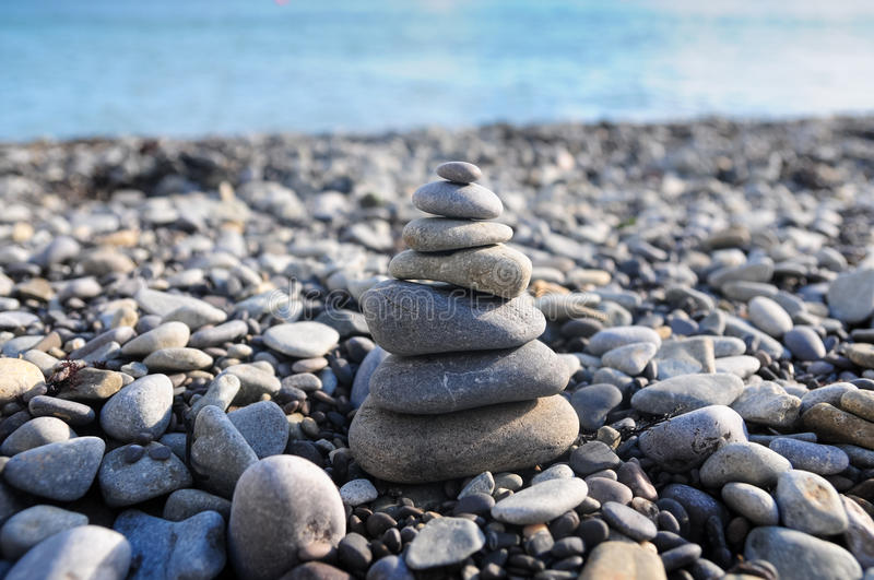 Pyramid of pebble stones. Stone stack on pebble beach stock image