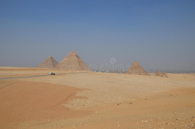 Pyramid in sand dust under gray clouds stock photos