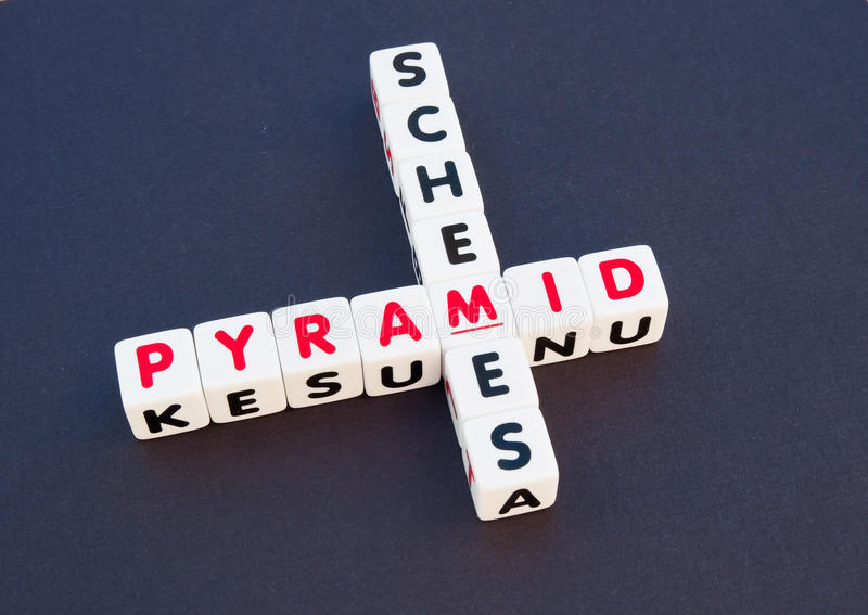 Pyramid scheme. Text 'pyramid scheme' inscribed in uppercase letters on small white cubes then arranged jigsaw fashion on a dark background, concept of a swindle stock photography